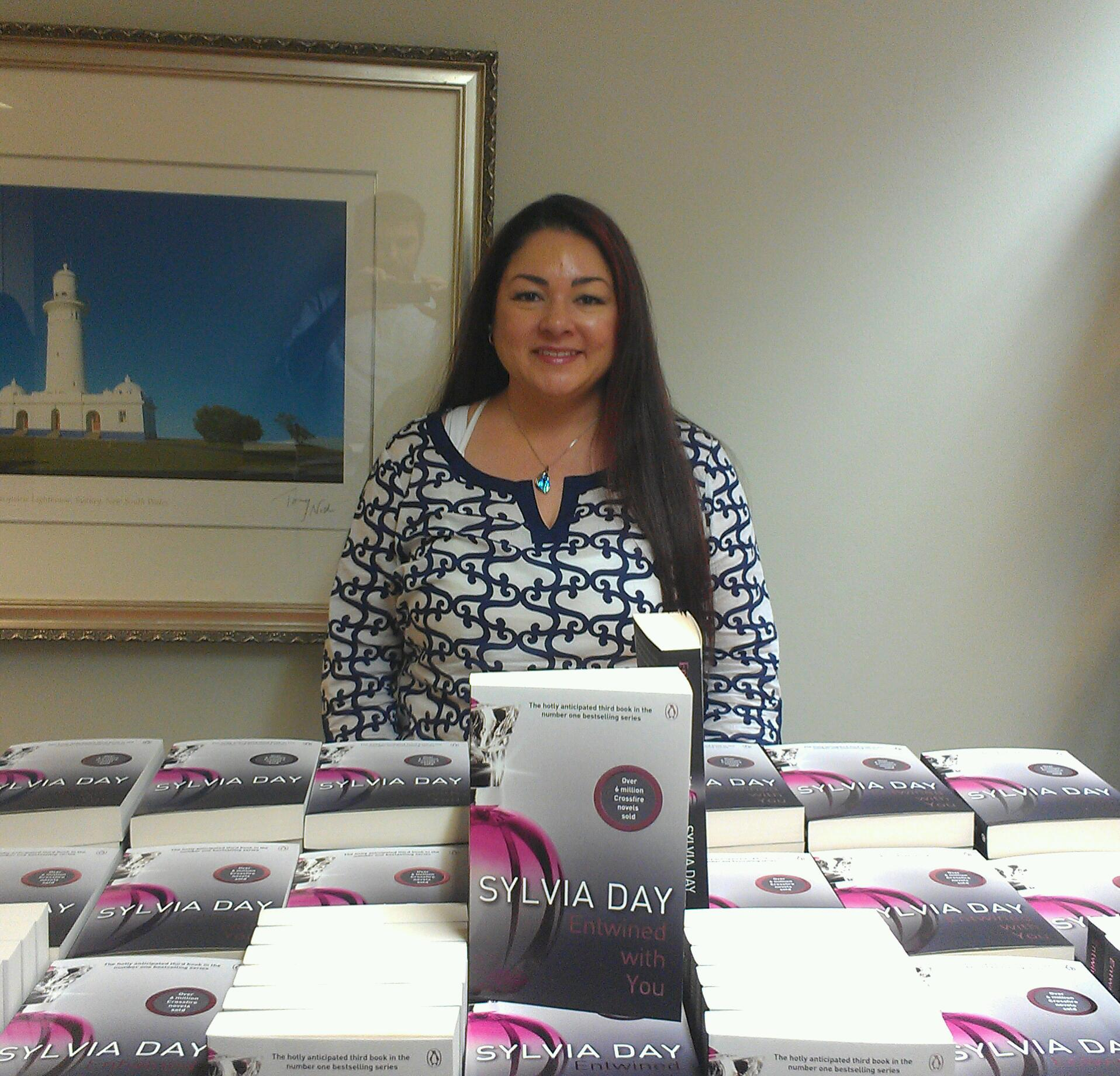 Sylvia Day at Booktopia with a huge pile of Entwined with You